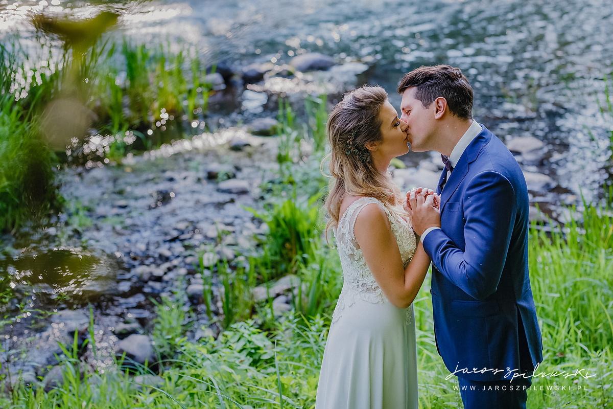 Para trzymająca się za ręce na tle przyrody.